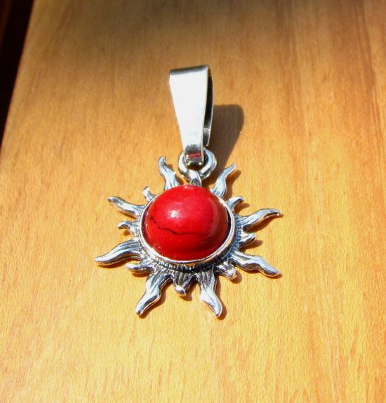 Indian silver jewelry pendant in sun shape with coral